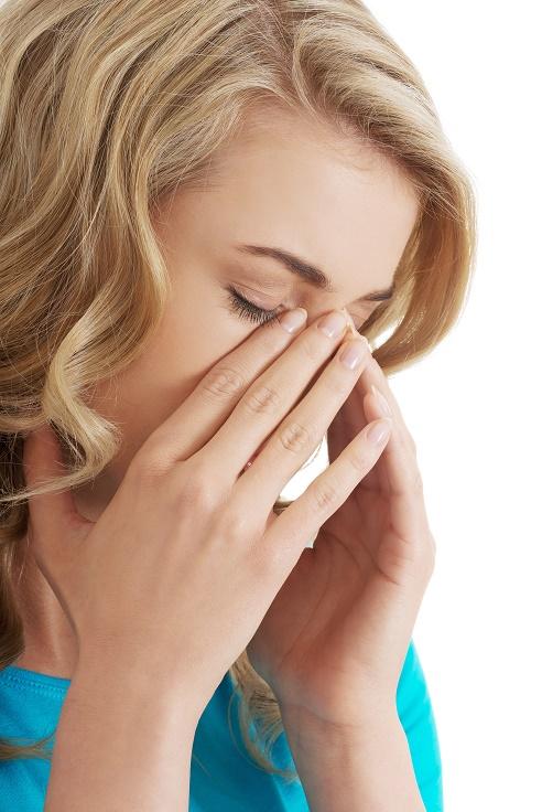 Woman experiencing sinus pain.