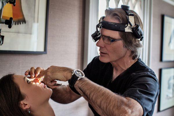 Dr.Oakley Smith examining patients nose
